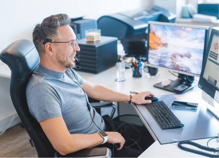 kundenbretreuer sitzt vor monitor mit headset