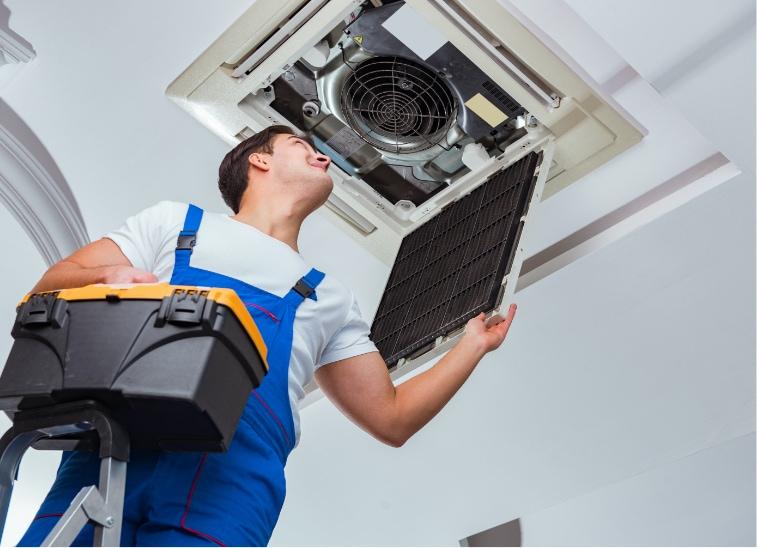 Arbeiter auf Treppe begutachtet Klimagerät